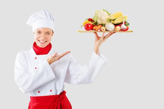 Cook segura em uma das mãos uma bandeja de madeira. cozinhe com vegetais proibidos na montanha