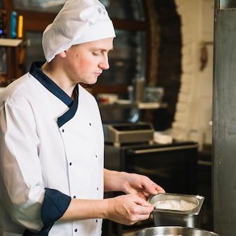 Cook segurando o recipiente com molho