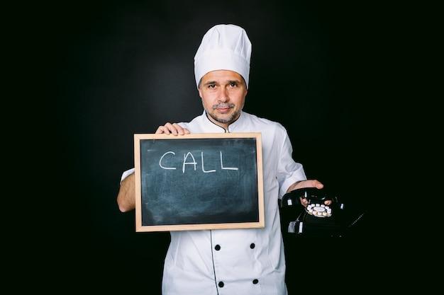 Cook, vestido com uma jaqueta branca e chapéu, segura uma lousa que diz: