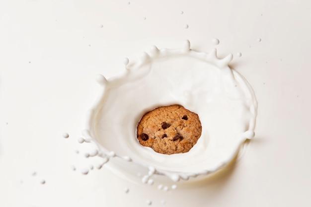 Cookie de chocolate caindo e espirrando no leite.