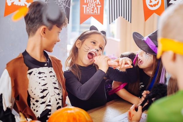 Cookie de halloween. engraçada linda garota de cabelos escuros com cara de gato pintada tentando doce mão cookie de halloween