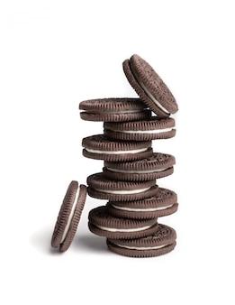 Cookie e cookies de chocolate creme na pilha e peças únicas no fundo branco