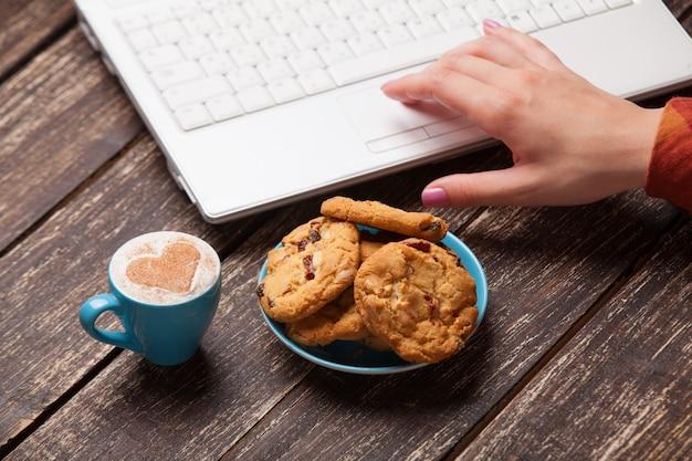 Cookie e mulheres mão com notebook.