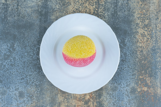 Cookie em forma de pêssegos no prato, na superfície do mármore.