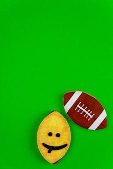 Cookie oval de cara engraçada como uma bola de futebol americano isolada sobre fundo verde. vista do topo.