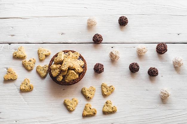 Cookies caseiros com sementes de açafrão e linho em forma de coração em quadros brancos com uma cesta e emaranhados de videira. comida para o dia dos namorados. vista de cima.