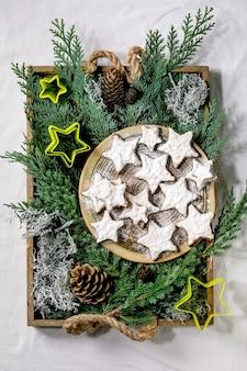 Cookies caseiros de amêndoa de cacau em forma de estrela com esmalte branco e açúcar de confeiteiro. na placa de cerâmica com cortadores de biscoitos de estrelas de natal, ramos de thuja, decorações sobre toalha de mesa branca. postura plana