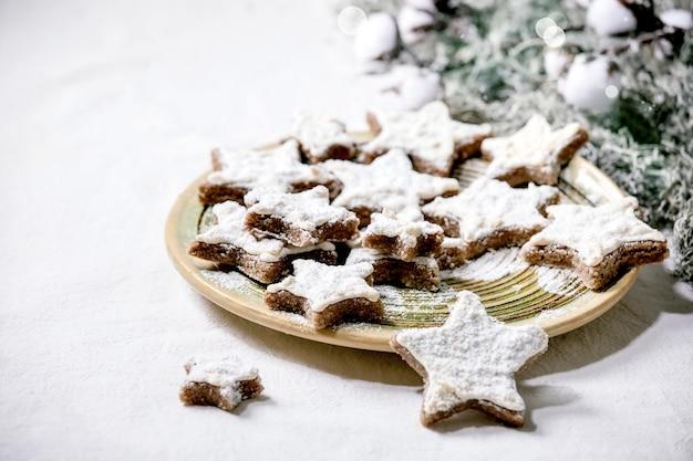 Cookies caseiros de amêndoa de cacau em forma de estrela com esmalte branco e açúcar de confeiteiro. na placa de cerâmica com decorações de ramos verdes sobre toalha de mesa branca. copie o espaço