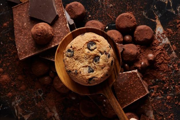 Cookies caseiros de chocolate em uma colher de pau com cacau em pó e doces