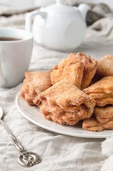 Cookies caseiros de triângulo com recheio de requeijão polvilhado com açúcar. num prato branco. linho cinza de fundo. no fundo está um antigo bule e uma xícara.