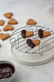 Cookies caseiros em formato de coração com cobertura de chocolate amargo