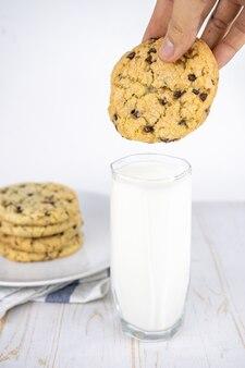 Cookies clássicos de chocolate recém-assados com nozes em um prato e um copo de leite