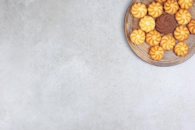 Cookies colocados em formação de estrelas em uma bandeja de madeira na superfície de mármore