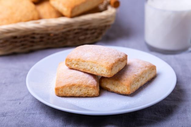 Cookies com açúcar de confeiteiro em um prato branco. no fundo, uma cesta de biscoitos e um copo de leite. fechar-se.