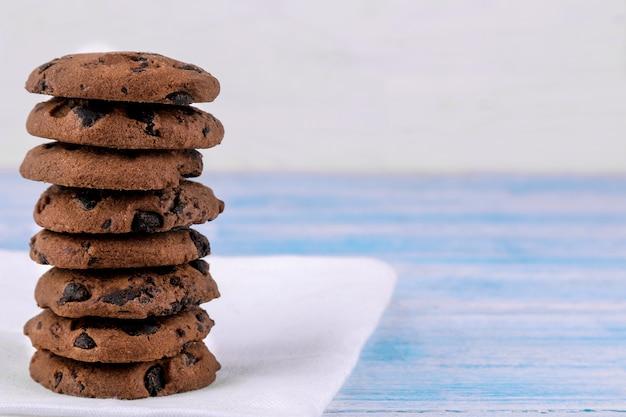 Cookies com chocolate dobrado em uma pilha em um guardanapo branco sobre uma mesa de madeira azul. assar. gostoso. espaço para texto