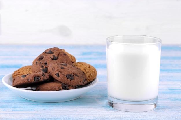 Cookies com chocolate em um prato e leite em um copo sobre um fundo azul de madeira. cozimento. gostoso