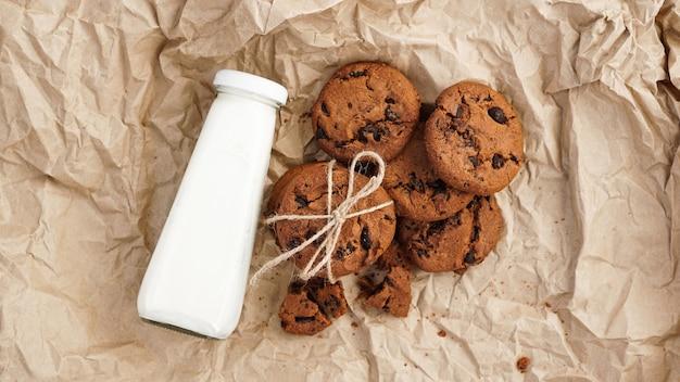 Cookies com gotas de chocolate em papel artesanal e garrafa de leite. cobras orgânicas artesanais naturais para café da manhã saudável