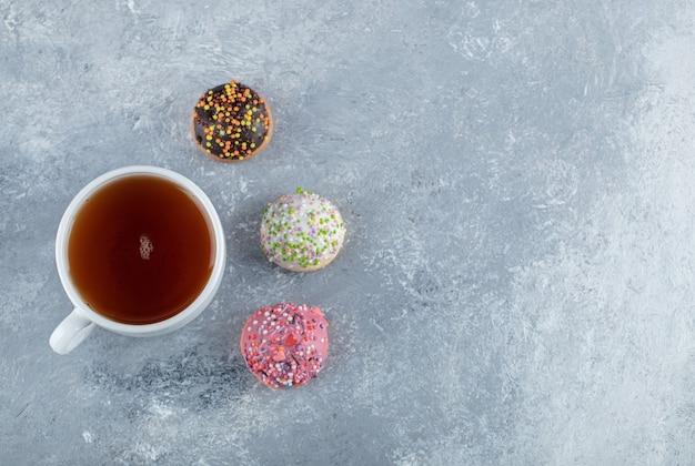 Cookies com granulado e xícara de chá na mesa de mármore.