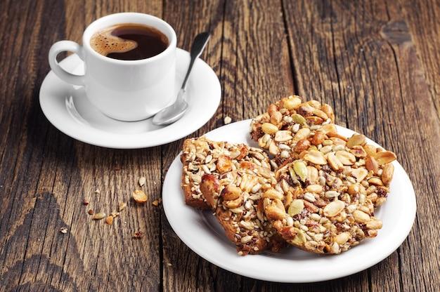 Cookies com nozes e xícara de café na velha mesa de madeira