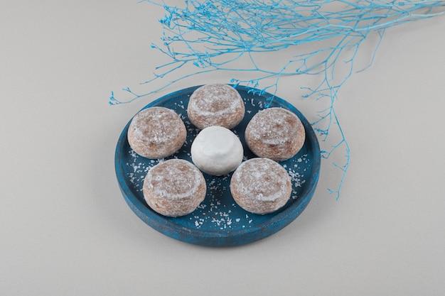 Cookies com revestimento em pó de baunilha em uma pequena bandeja ao lado de galhos azuis sobre fundo de mármore.
