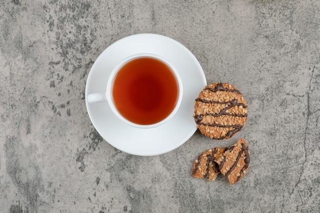 Cookies com sementes de gergelim e duas xícaras de chá na superfície de mármore.