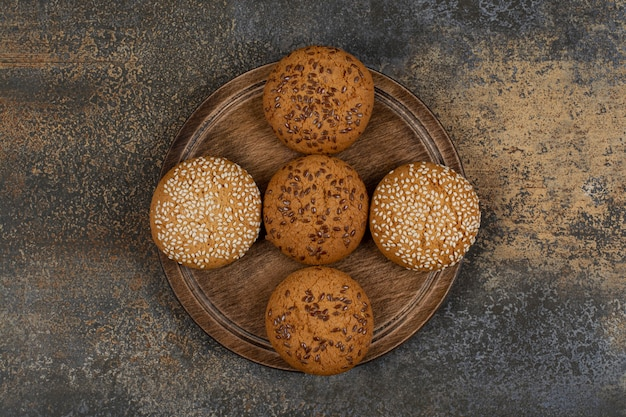 Cookies com sementes de gergelim e pedaços de chocolate na placa de madeira.