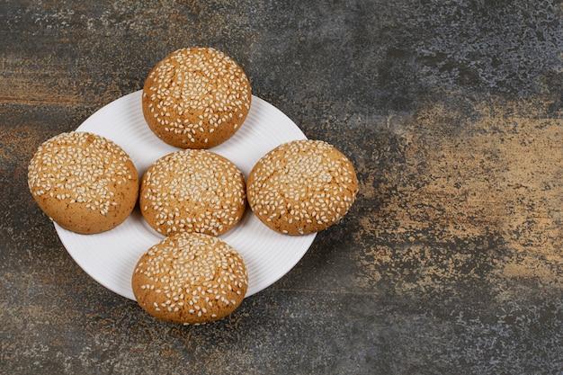 Cookies com sementes de gergelim na chapa branca.