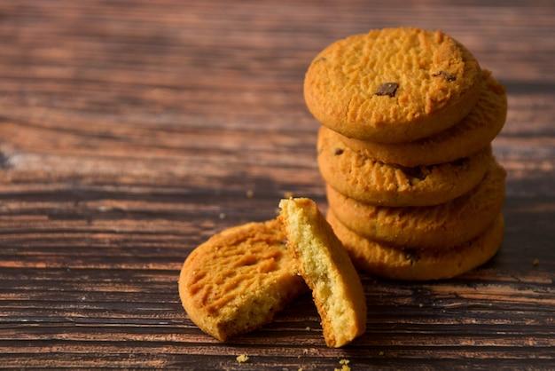 Cookies da aveia e dos pedaços de chocolate no fundo de madeira rústico da tabela, espaço da cópia.