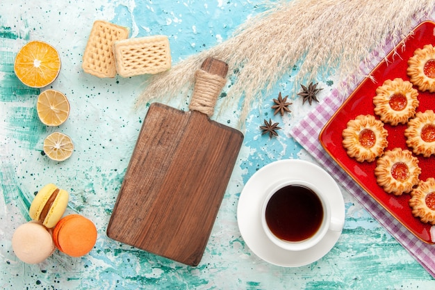 Cookies de açúcar de vista de cima dentro de um prato vermelho com uma xícara de chá e macarons no fundo azul