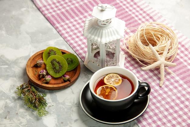 Cookies de açúcar de vista frontal com uma xícara de chá na superfície branca