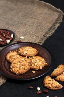 Cookies de amendoim caseiros em um prato marrom com amendoim cru no fundo. comida de estilo rústico.