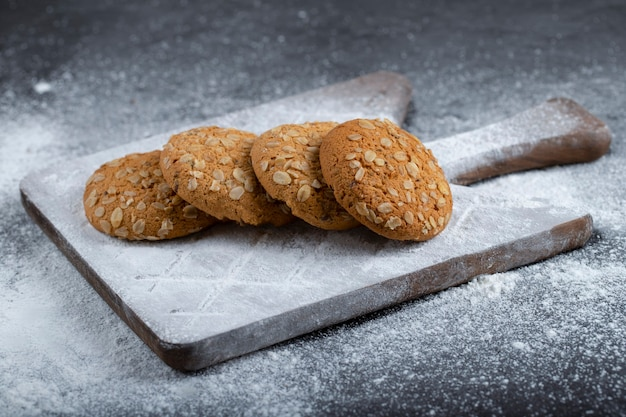 Cookies de aveia com açúcar em pó em um fundo preto.