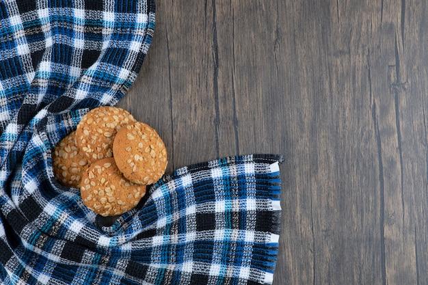 Cookies de aveia com cereais e sementes colocadas sobre uma mesa de madeira.
