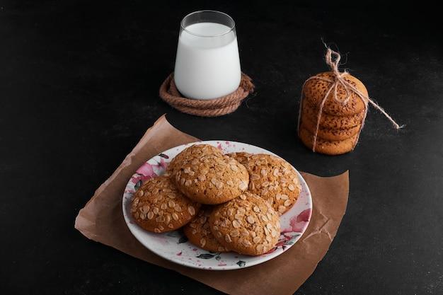 Cookies de aveia com cominho preto e um copo de leite à parte.