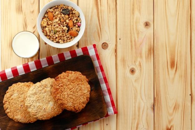 Cookies de aveia com flocos de aveia e copo de leite na mesa de madeira