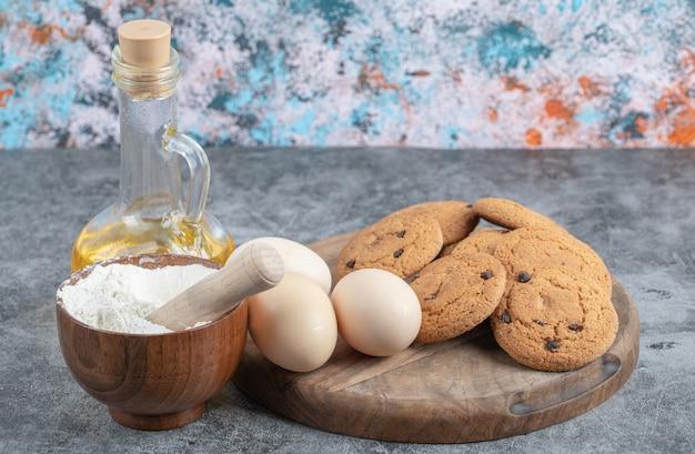 Cookies de aveia com gotas de chocolate em uma placa de madeira com ingredientes ao redor