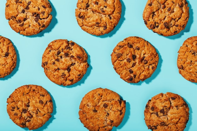 Cookies de aveia com padrão de gotas de chocolate e padrões sobre um fundo azul claro.
