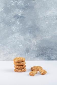 Cookies de aveia com sementes de gergelim em uma mesa branca.