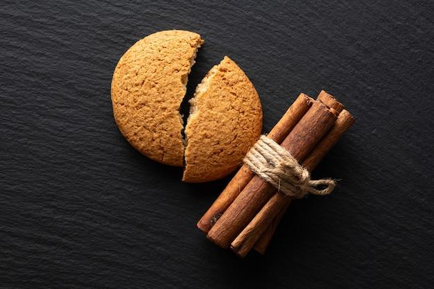 Cookies de aveia quebrados e canela em uma superfície de pedra, plana