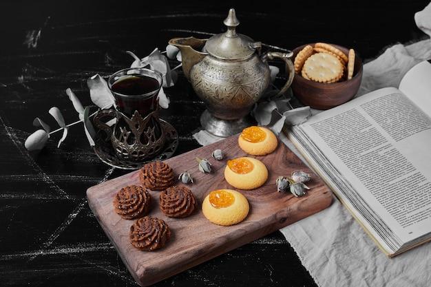 Cookies de cacau e manteiga em uma placa de madeira com chá.