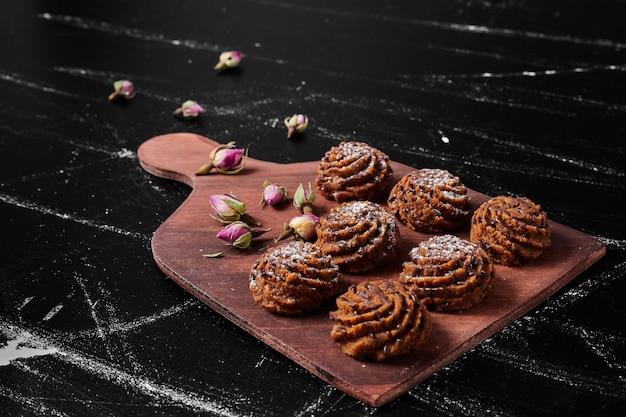 Cookies de cacau em uma placa de madeira.