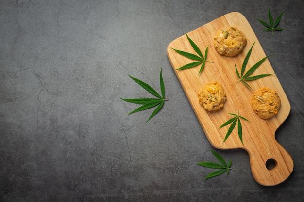 Cookies de cannabis e folhas de cannabis colocados em uma tábua de madeira