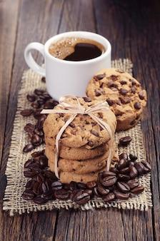 Cookies de chocolate amarrados com uma fita e uma xícara de café na mesa de madeira escura