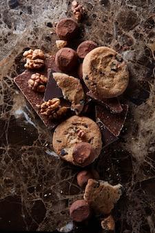 Cookies de chocolate com bombons de chocolate na superfície de mármore escuro.