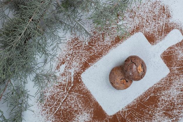 Cookies de chocolate com cacau em pó na superfície branca