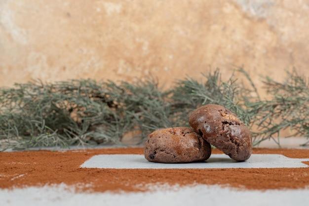 Cookies de chocolate com cacau em pó no fundo branco.