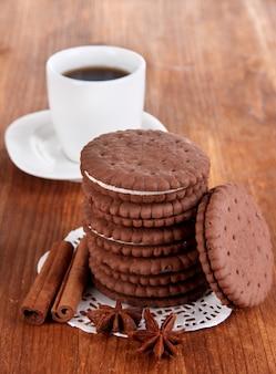 Cookies de chocolate com camada cremosa e xícara de café em close-up de mesa de madeira