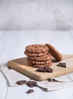 Cookies de chocolate com gotas de chocolate na tábua de madeira sobre uma mesa de luz. vista frontal e espaço de cópia