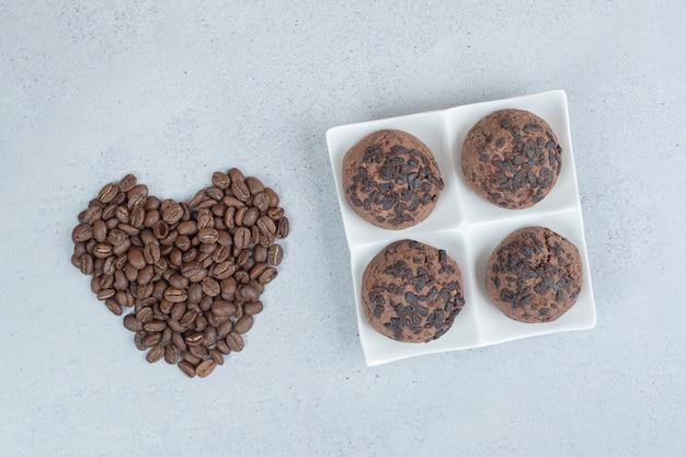 Cookies de chocolate com grãos de café na superfície branca