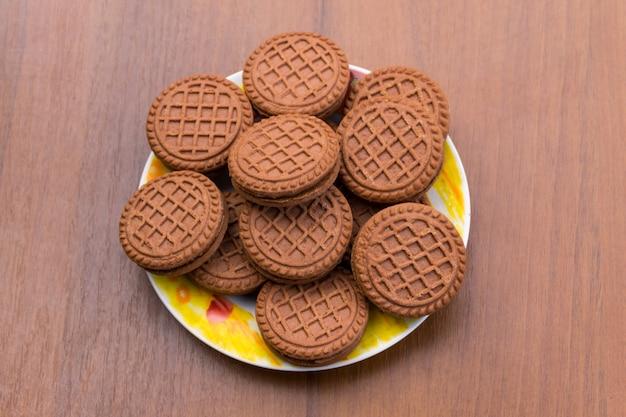 Cookies de chocolate com recheio de creme na mesa de madeira. vista do topo
